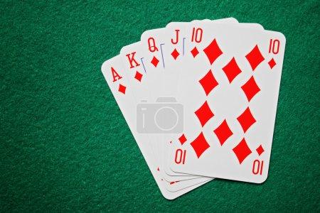 Royal straight flush poker cards on a green felt t...