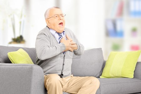 Photo for Senior man seated on a sofa having a heart attack at home - Royalty Free Image