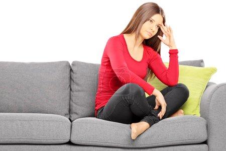 Sad woman sitting on modern sofa