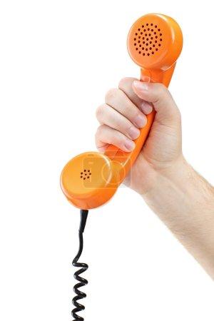 Photo pour Main tenant un vieux tube téléphonique orange isolé sur fond blanc - image libre de droit