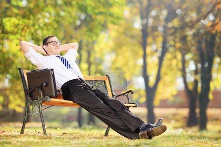 Photo pour Jeune homme d'affaires faisant une pause après le travail assis sur un banc dans le parc - image libre de droit