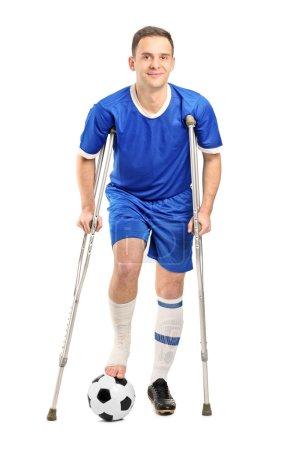 Foto de Retrato de cuerpo entero de un jugador de fútbol fútbol lesionado en muletas aislado sobre fondo blanco - Imagen libre de derechos