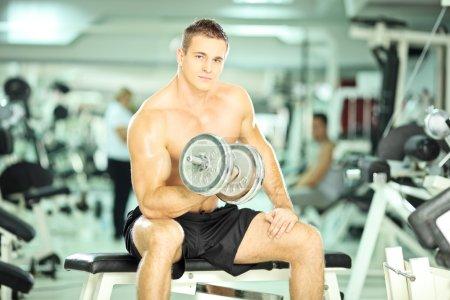 Photo pour Homme musclé torse nu soulevant des poids dans une salle de gym - image libre de droit