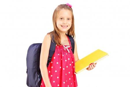 Photo pour Une écolière tenant un carnet, isolée sur fond blanc - image libre de droit