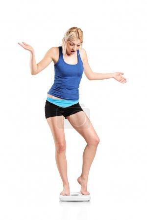 Photo pour Une jeune femelle déçue sur une échelle de poids isolée sur fond blanc - image libre de droit