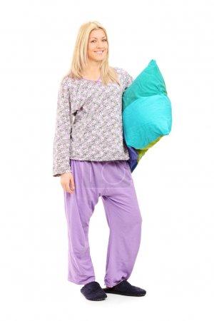 Photo pour Portrait de toute la longueur d'une fille blonde en pyjama tenant un oreiller isolé sur fond blanc - image libre de droit