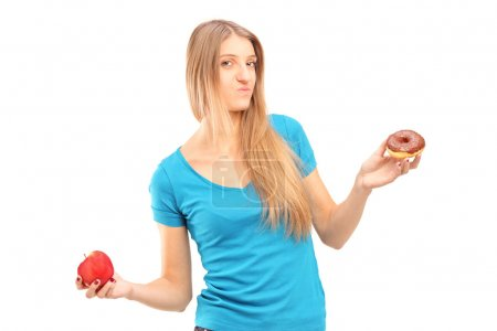 Doubtful female holding an apple and donut
