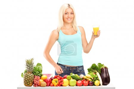 Photo pour Belle jeune femme tenant un verre de jus derrière une table pleine de fruits et légumes isolés sur fond blanc - image libre de droit