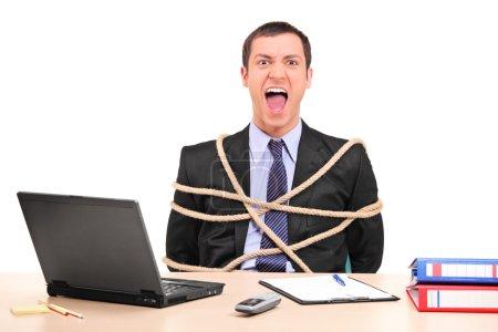 Photo pour Un homme d'affaires ligoté avec une corde au bureau isolé sur fond blanc - image libre de droit
