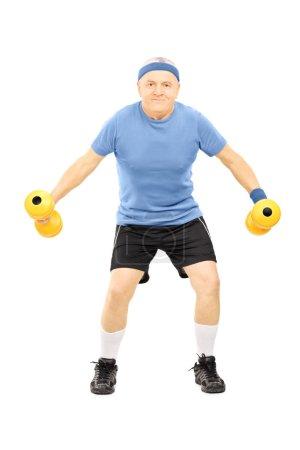 Photo pour Portrait complet d'un homme mature en tenue de sport s'exerçant avec des haltères isolés sur fond blanc - image libre de droit