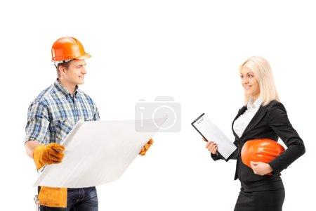 Photo pour Ingénieur tenant un plan et discutant avec une architecte féminine isolée sur fond blanc - image libre de droit