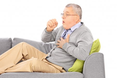 Man seated on sofa coughing