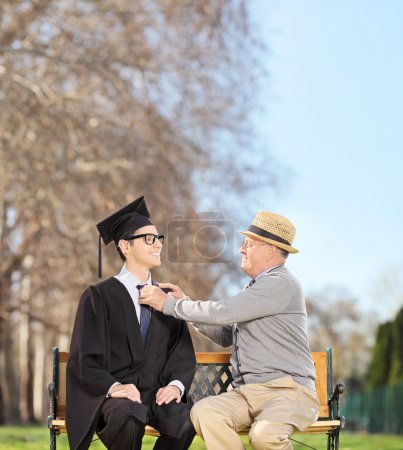 Student and father sitting in park