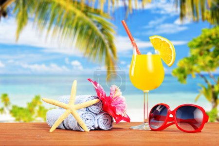 Photo for Orange cocktail and other summer accessories on a beach table with palm tree in the background - Royalty Free Image
