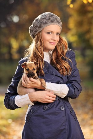 Woman smiling and holding puppy