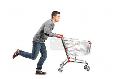 Man pushing an empty shopping cart