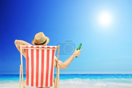 Man on beach chair holding beer