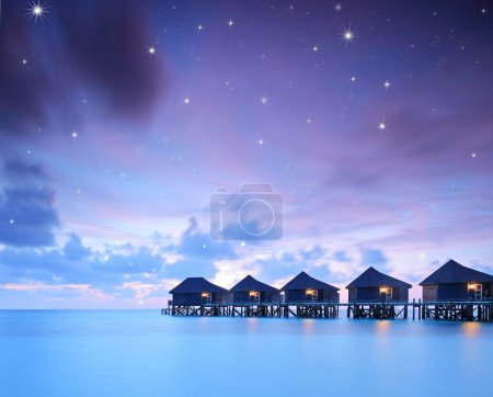 Starry skies over water villa cottages