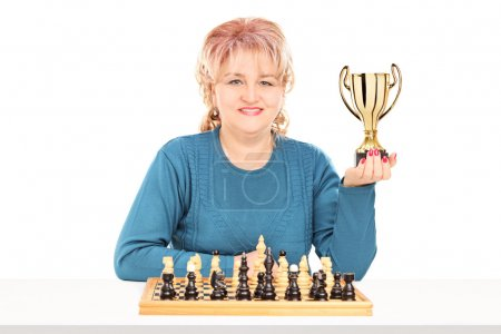 Female chess player holding trophy