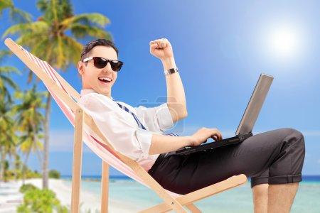 Businessman with laptop on beach
