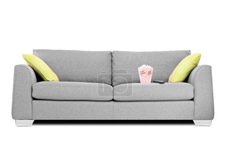 Photo pour Studio plan d'un canapé moderne avec boîte de pop-corn sur elle isolé sur fond blanc - image libre de droit