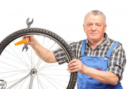 man repairing bicycle wheel