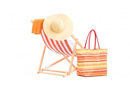 Sun lounger with orange stripes and summer accesso...