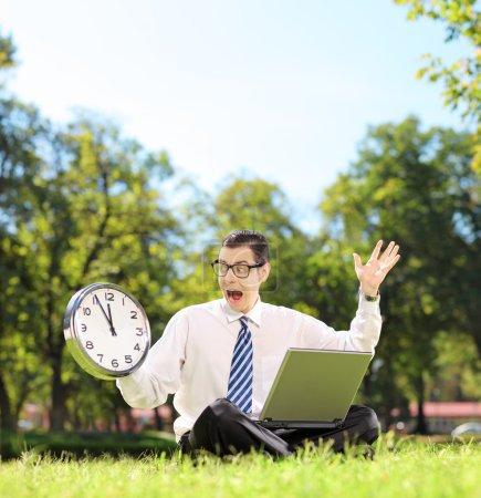 Wütender Geschäftsmann mit Laptop im Park
