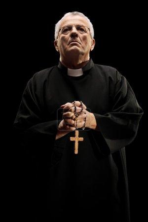 Catholic reverend holding wooden cross