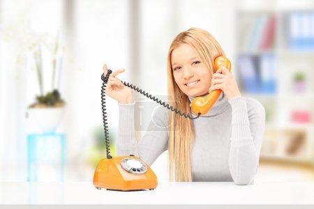 Photo pour Jeune femme souriante parlant sur un vieux téléphone de style à la maison - image libre de droit