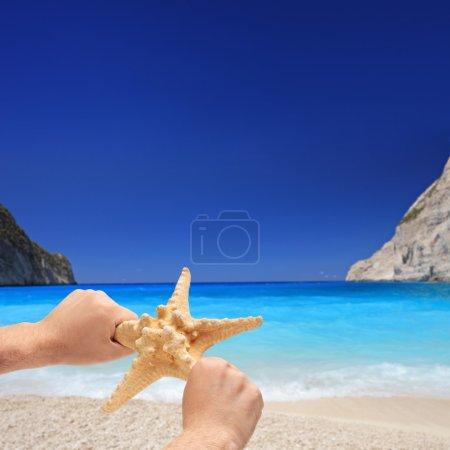 Photo pour Personne tenant une étoile de mer sur une plage de sable fin sur l'île de Zakynthos, Grèce - image libre de droit