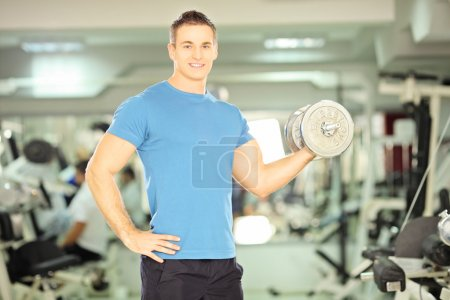 Photo for Smiling muscular man lifting weight in a fitness club - Royalty Free Image