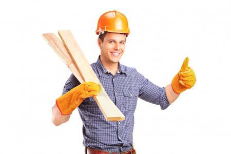 Photo for A smiling manual carpenter holding sills and giving thumb up isolated on white background - Royalty Free Image