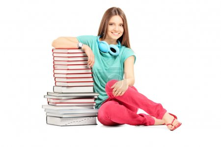 Photo for Smiling female student with headphones sitting near a pile of books isolated on white background - Royalty Free Image