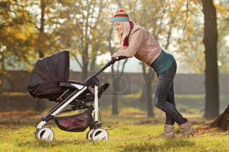Mother with a baby carriage in a park