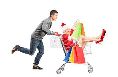 Guy pushing female in cart