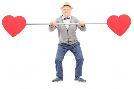 Photo for Senior gentleman holding a pipe with hearts on both ends isolated on white background - Royalty Free Image