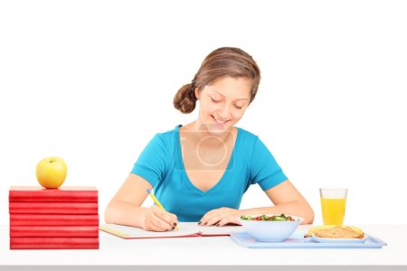 Girl writing homework and having meal
