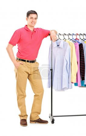 Photo for Full length portrait of a smiling guy posing on a hang rail full of clothes isolated on white background - Royalty Free Image