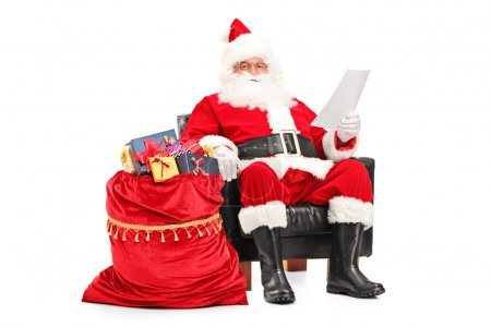 Photo for Santa Claus sitting in armchair and reading a letter next to a bag full of gifts isolated on white background - Royalty Free Image