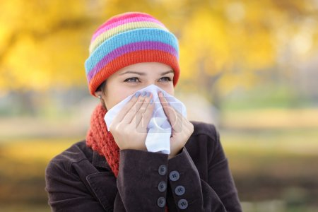 Young woman with tissue having flu or allergy...