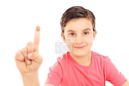 Photo pour Petit enfant montrant son doigt bandé isolé sur fond blanc - image libre de droit