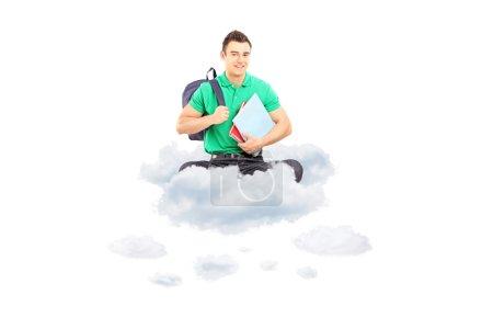 Foto de Joven estudiante masculino con bolso escolar y cuadernos sentados en una nube aislada sobre fondo blanco - Imagen libre de derechos