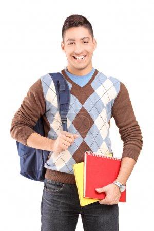 Photo pour Un bel étudiant masculin avec un sac d'école contenant des livres isolés sur fond blanc - image libre de droit