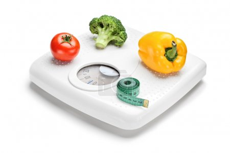 Vegetables and measuring tape on scale