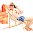 Man enjoying on a sun lounger while talking on a m...