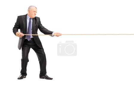 Mature businessman pulling rope