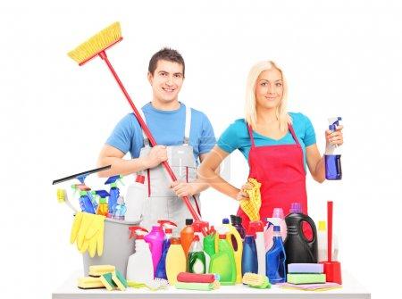 Photo pour Nettoyants masculins et féminins posant avec nettoyage fournitures sur une table isolé sur fond blanc - image libre de droit