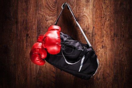 Photo pour Sac de sport et les gants de boxe, accroché sur un mur en bois - image libre de droit