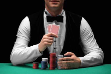 A man with bow tie holding cards and gambling chip...